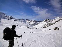 Male backcountry skier looks at mountain landscape and his goal for the day`s backcountry ski tour. A male backcountry skier looks at mountain landscape and his Royalty Free Stock Photography