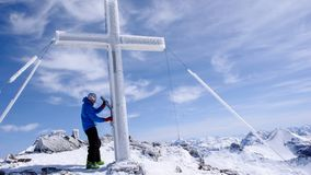 Male backcountry skier at the summit cross of a high alpine peak on a beautiful winter day. A male backcountry skier at the summit cross of a high alpine peak on Stock Images