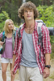 Male backpacker looking away with woman standing in background at forest Stock Photography