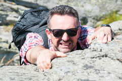 Male backpacker making effort climbing a rock Stock Images