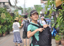 Male backpacker opening camera bag on street Stock Image