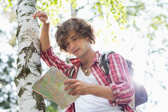 Male backpacker reading map while leaning on tree trunk in forest Stock Photos