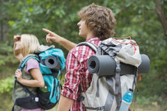 Male backpacker showing something to woman in forest Stock Photo