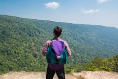 Male Backpacker Stand on cliff while Travel Trekking Trip over G Royalty Free Stock Photo