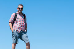 Male backpacker standing with blue sky background Royalty Free Stock Photos