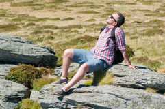 Male backpacker sun bathing on top of the mountain Royalty Free Stock Image