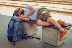 Male backpacker tourist napping on a bench. Handsome male backpacker tourist napping on a bench and baggage at the station Stock Photos