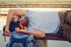 Male backpacker tourist napping on a bench. Handsome male backpacker tourist napping on a bench and baggage at the station Stock Photo