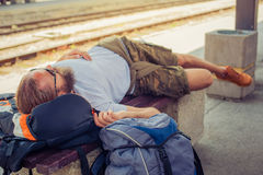 Male backpacker tourist napping on a bench. Handsome male backpacker tourist napping on a bench and baggage at the station Royalty Free Stock Image