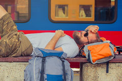 Male backpacker tourist napping on a bench Stock Photography