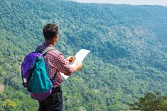 Male Backpacker Traveler or Trekker Stand on Cliff use Navigatio. N map and Compass while Hiking on Green Nature Mountain as Traveling Equipment Concept Stock Photography