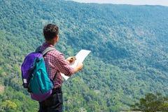 Male Backpacker Traveler or Trekker Stand on Cliff use Navigatio Stock Photography