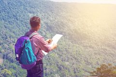 Male Backpacker Traveler or Trekker Stand on Cliff use Navigatio. N map and Compass while Hiking on Green Nature Mountain as Traveling Equipment Concept Stock Images