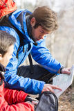 Male backpackers reading map in forest Stock Photos