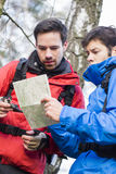 Male backpackers reading map together in forest Royalty Free Stock Image
