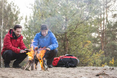 Male backpackers warming hands at campfire in forest Royalty Free Stock Photography