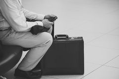 Male with baggage and phone. Closeup passanger tourist male figure in striped shirt trousers cosy shoes with black colored baggage coat and phone sitting in Royalty Free Stock Photo