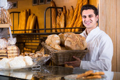 Male baker at bakery. Portrait of friendly smiling male baker at bakery display with bread stock photography