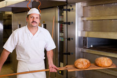 Male baker baking bread. Male baker baking fresh bread in the bakehouse Royalty Free Stock Photography