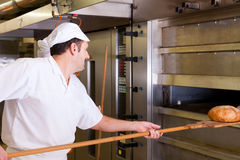 Male baker baking bread. Male baker baking fresh bread in the bakehouse Stock Photography