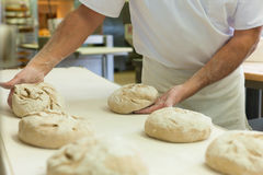 Male baker baking bread. Male baker baking fresh bread in the bakehouse Stock Photo