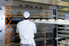 Male baker baking bread. Male baker baking fresh bread in the bakehouse Royalty Free Stock Photo