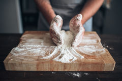 Male baker hands kneading dough on cutting board Royalty Free Stock Photography