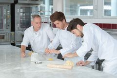Male baker and assistants. Male baker and his assistants stock photography
