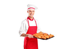 A male baker holding freshly baked croissants Stock Photography