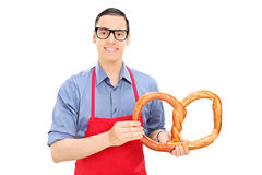 Male baker holding a huge pretzel Royalty Free Stock Image