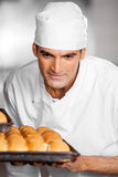 Male Baker Looking At Freshly Baked Breads In Baking Tray Stock Photo