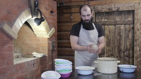 Male Baker making handmade bread next to the stove stock video footage