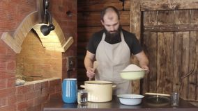 Male Baker pours into the pan the ingredients to kneading the dough stock video footage