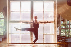Male ballet dancer is dancing in front of a window royalty free stock images