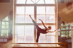 Male ballet dancer is dancing in front of a window. Male ballet dancer is dancing in front of a large window, standing on the windowsill stock image