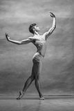 The male ballet dancer posing over gray background. Colorless image royalty free stock images