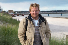 Male at Baltic Beach Germany. Handsome blond male is standing in autumn at the baltic sea beach with some grasses and the bridge to Fehmarn Royalty Free Stock Photography