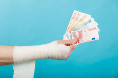Male bandaged hand with money. Corruption in healthcare industry. Part body male bandaged hand with money and long white bandage on blue royalty free stock images
