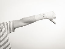 Male bandaged hand with thumb down sign. Stock Photo