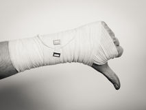 Male bandaged hand with thumb down sign. Stock Photography