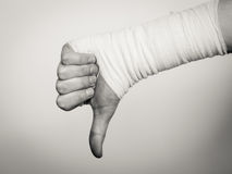 Male bandaged hand with thumb down sign. Stock Photos