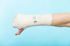 Male bandaged hand with thumb down sign. Stock Images