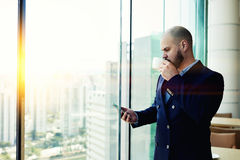 Male banker is standing near office window background with copy space for your advertising. Bearded man professional banker is enjoying coffee and monitoring the Stock Image