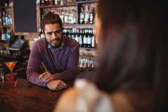 Male bar tender interacting with customer at pub Royalty Free Stock Photo