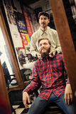 Male barber checking symmetry beard. On client Stock Photos