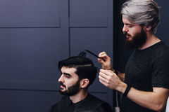 Male barber combing and shaving hair of a male client Royalty Free Stock Photo