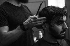Male barber combing and shaving hair of a male client Stock Photos