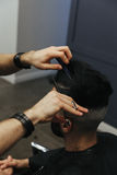 Male barber combing and shaving hair of a male client Royalty Free Stock Photography