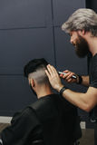 Male barber combing and shaving hair of a male client Royalty Free Stock Photos