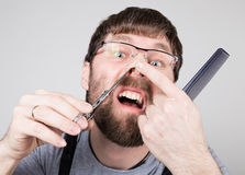 Male barber cuts his own hair in the nose, looking at the camera like the mirror. stylish professional hairdresser Royalty Free Stock Images